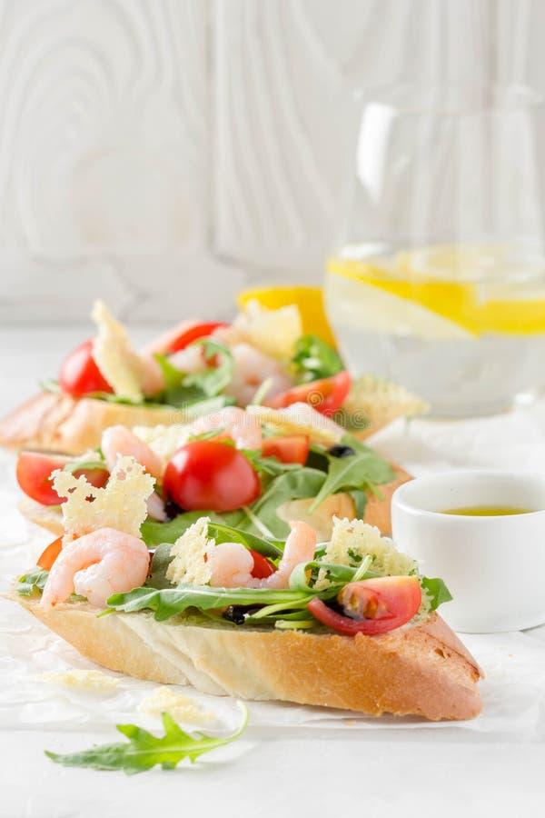 Bruschette avec l'arugula, la crevette, les tomates-cerises et le vinaigre balsamique Trois sandwichs ouverts savoureux pour le d image libre de droits