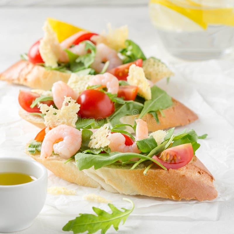 Bruschette avec l'arugula, la crevette, les tomates-cerises et le vinaigre balsamique Trois sandwichs ouverts savoureux pour le d photos libres de droits