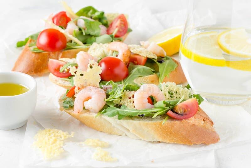 Bruschette avec l'arugula, la crevette, les tomates-cerises et le vinaigre balsamique Trois sandwichs ouverts savoureux pour le d photos stock