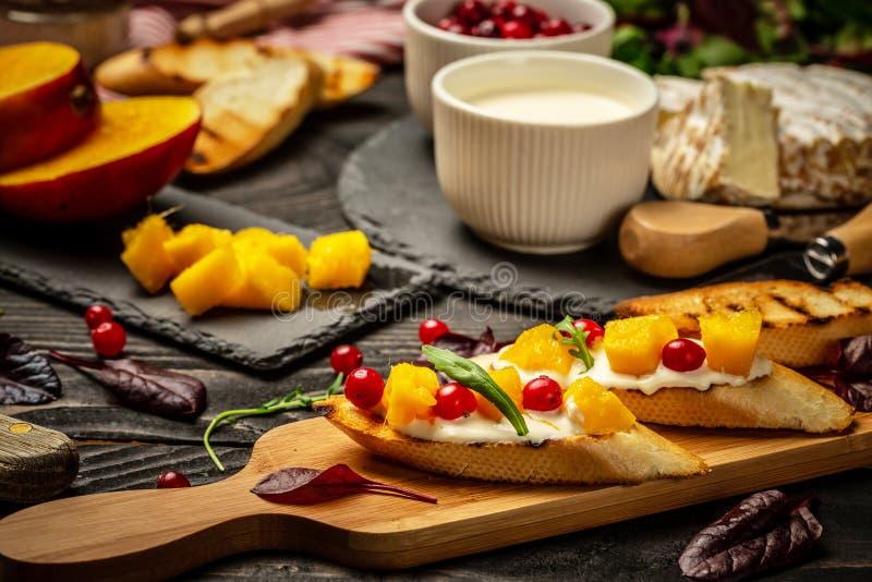 Bruschette avec la mangue coupée, fromage crémeux de Ricotta sur la baguette fraîche sur la table Le concept de la consommation s images libres de droits