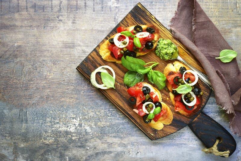 Bruschette avec la tomate, les olives noires, les câpres et le pesto de sauce photos stock