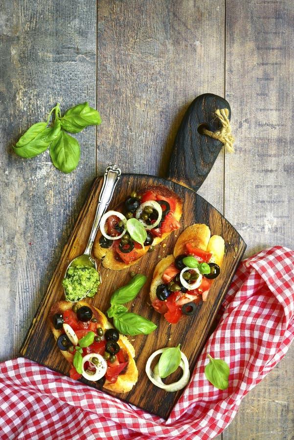 Bruschette avec la tomate, les olives noires, les câpres et le pesto de sauce image libre de droits