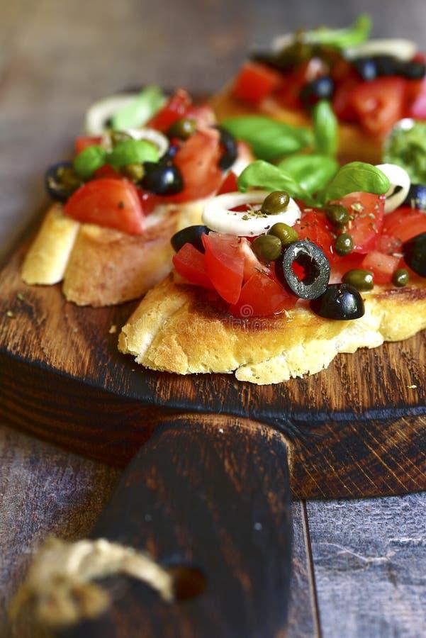 Bruschette avec la tomate, les olives noires, les câpres et le pesto de sauce photo stock