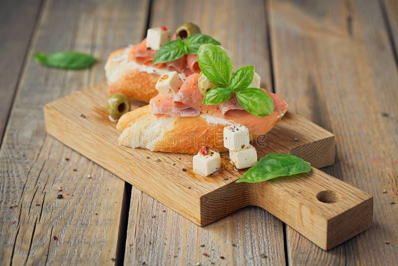 Bruschette avec le fromage de saumon et fondu fumé, les olives et l'arugula photo libre de droits