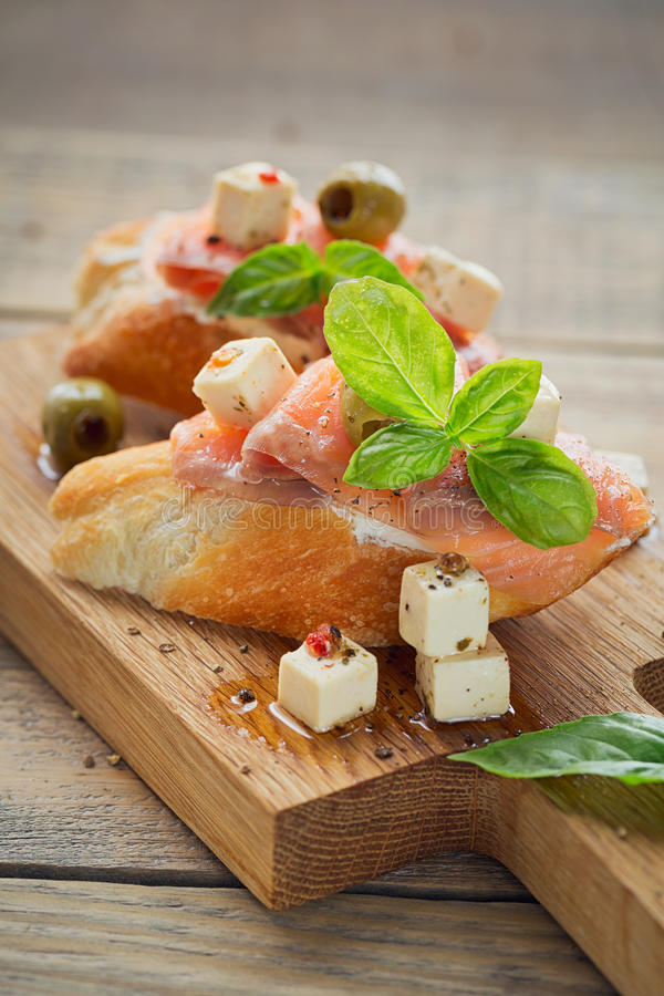 Bruschette avec le fromage de saumon et fondu fumé, les olives et l'arugula images stock