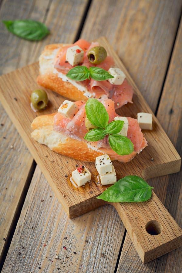 Bruschette avec le fromage de saumon et fondu fumé, les olives et l'arugula image stock