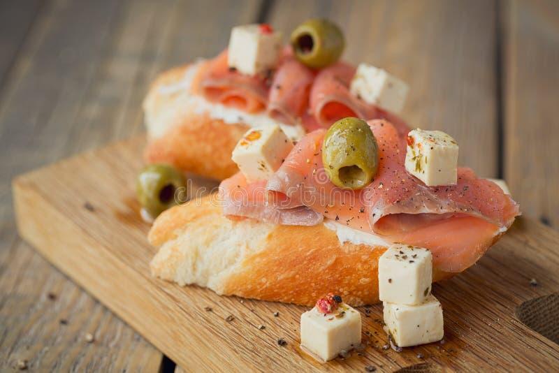 Bruschette avec le fromage de saumon et fondu fumé, les olives et l'arugula image libre de droits