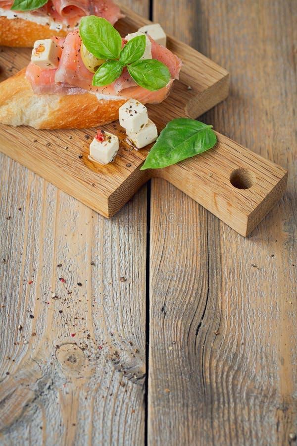 Bruschette avec le fromage de saumon et fondu fumé, les olives et l'arugula photographie stock libre de droits