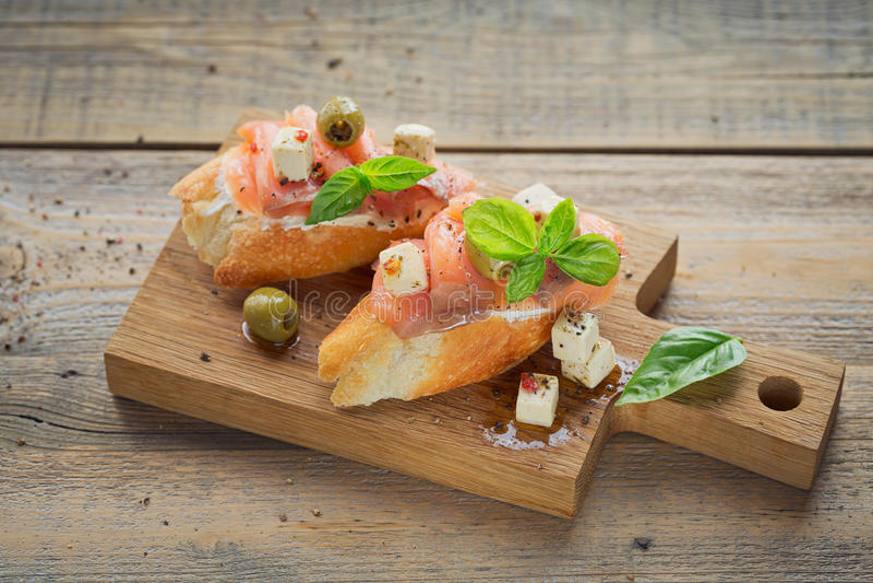 Bruschette avec le fromage de saumon et fondu fumé, les olives et l'arugula images libres de droits