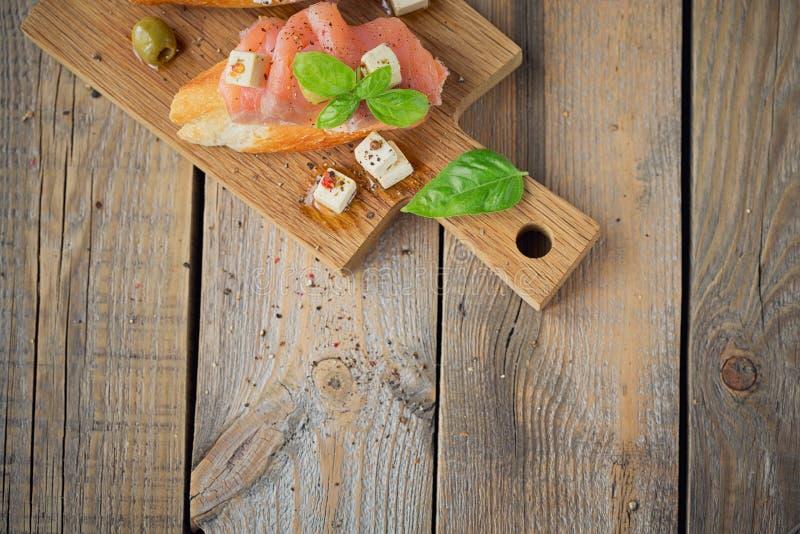 Bruschette avec le fromage de saumon et fondu fumé, les olives et l'arugula photos libres de droits