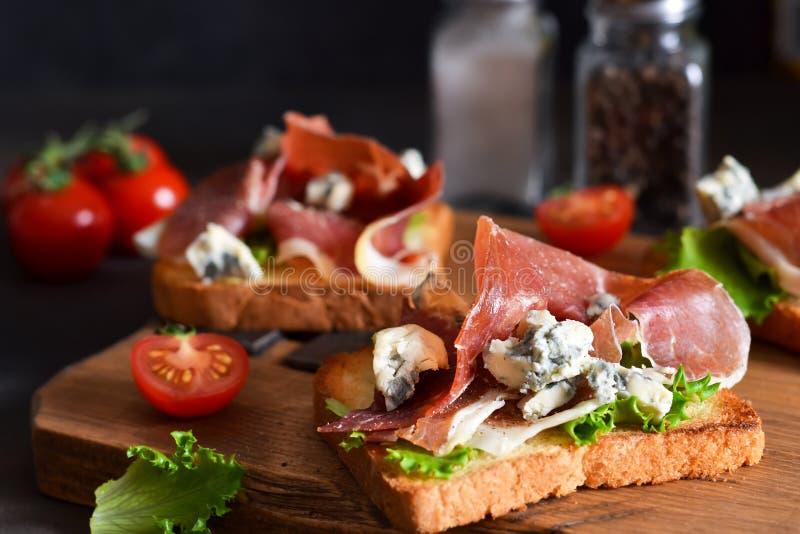 Bruschetta avec prosciutto, frise salade et fromage sur la table de la cuisine. Snack images libres de droits