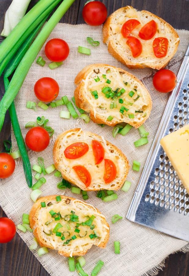Bruschette avec les tomates-cerises et l'oignon blanc images libres de droits