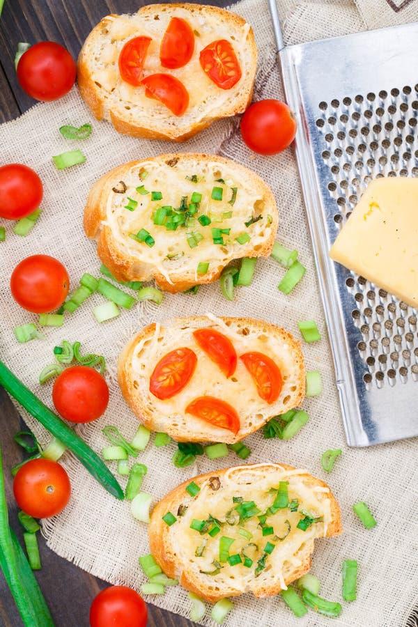 Bruschette avec les tomates-cerises et l'oignon blanc image libre de droits