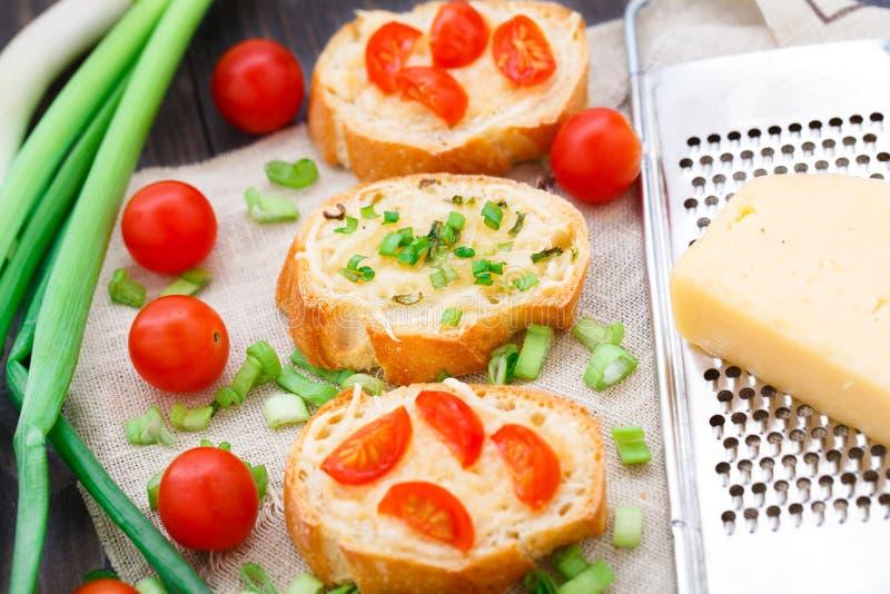 Bruschette avec les tomates-cerises et l'oignon blanc image stock