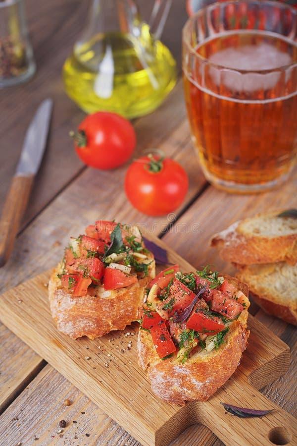 Bruschette avec les tomates, le basilic et les herbes coupés sur le cru grillé image libre de droits