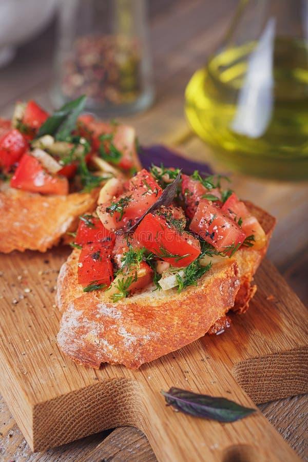 Bruschette avec les tomates, le basilic et les herbes coupés sur le cru grillé photos libres de droits