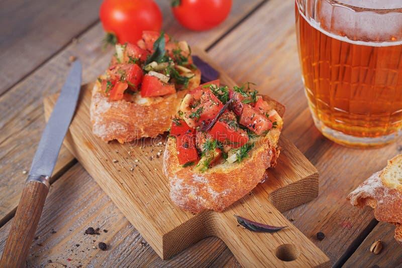 Bruschette avec les tomates, le basilic et les herbes coupés sur le cru grillé image stock