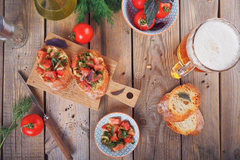 Bruschette avec les tomates, le basilic et les herbes coupés sur le cru grillé images stock