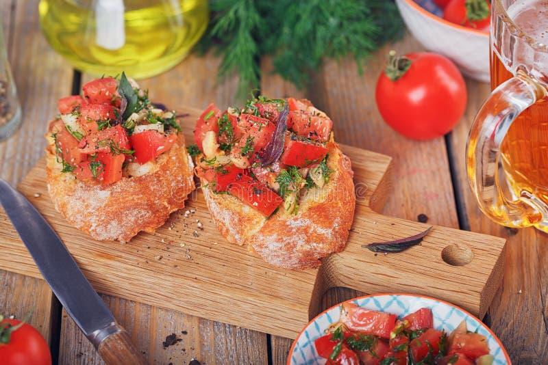 Bruschette avec les tomates, le basilic et les herbes coupés sur le cru grillé images libres de droits
