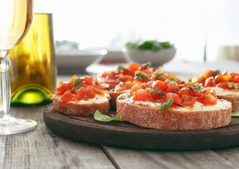 Bruschette avec les tomates, le fromage de chèvre et le basilic images libres de droits