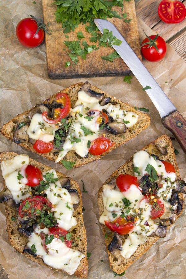 Bruschette avec les tomates, le fromage et les champignons image stock