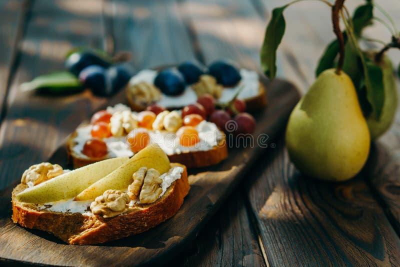 Bruschette con le prugne, le pere, l'uva e la ricotta fotografie stock