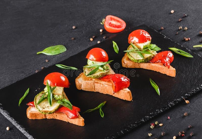 Bruschette d'apéritif avec des légumes, des tomates et des épices sur le panneau de schiste noir au-dessus du fond en pierre noir images stock