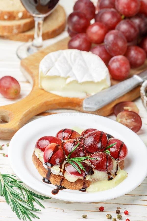 Bruschette de fromage de camembert ou de brie avec des raisins rouges, le romarin et balsamique image libre de droits