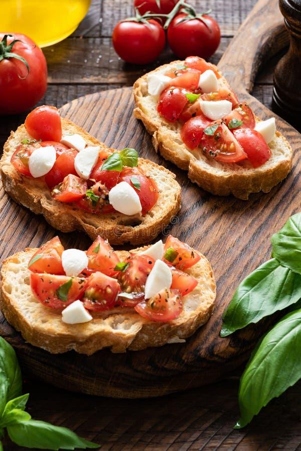 Bruschette de tomate et de mozzarella sur un conseil en bois photographie stock libre de droits