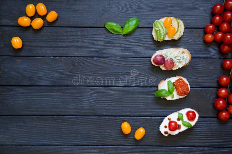 Bruschette dell'aperitivo con i pomodori, salmone, formaggio cremoso, basi immagini stock