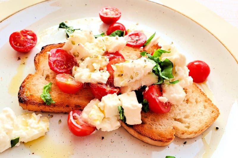 Bruschette italienne avec la tomate, le mozzarella, le basilic et l'huile d'olive frais, fin d'un plat blanc photo libre de droits