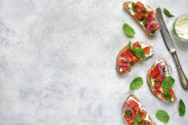 Bruschette italienne avec le fromage de tomate et fondu et les verts Vue supérieure images stock