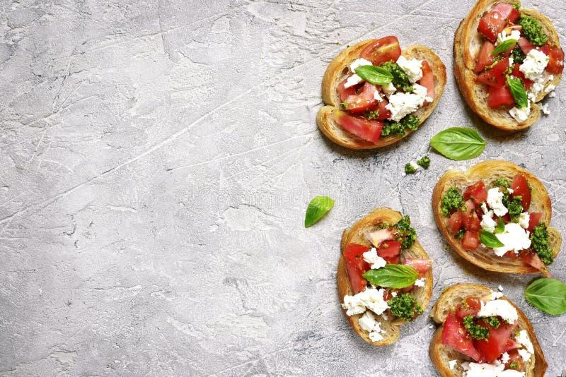 Bruschette italienne avec le pesto de tomates, de feta et de basilic Vue supérieure photographie stock libre de droits