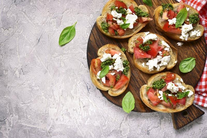 Bruschette italienne avec le pesto de tomates, de feta et de basilic Vue supérieure photo stock