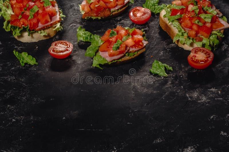 Bruschette italienne avec les tomates, la sauce ? mozzarella et les feuilles coup?es de salade Ap?ritif ou casse-cro?te italien t photo libre de droits