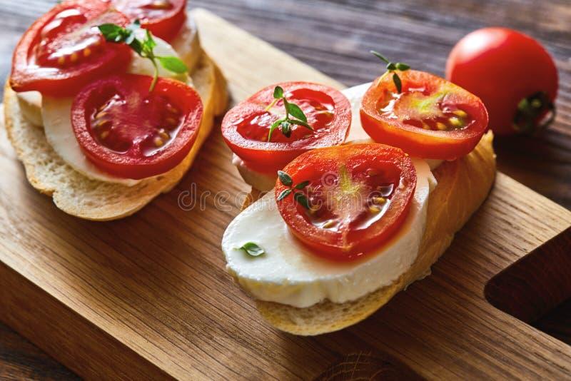 Bruschette italienne de tomate avec les légumes coupés, le mozzarella, les herbes et le pain croustillant de ciabatta sur un cons photo stock