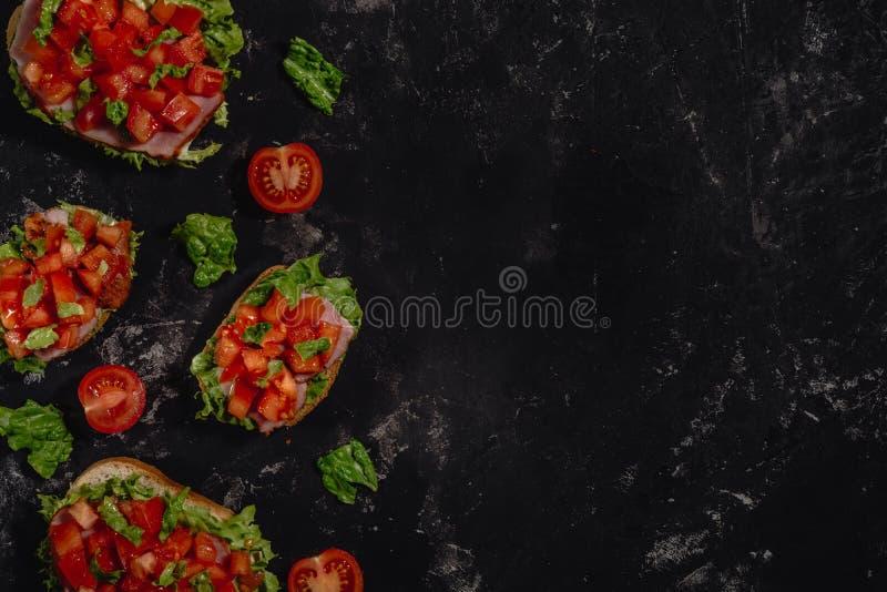 Bruschette italienne traditionnelle avec les tomates, la sauce ? mozzarella, les feuilles de salade et le jambon coup?s sur un fo photos libres de droits
