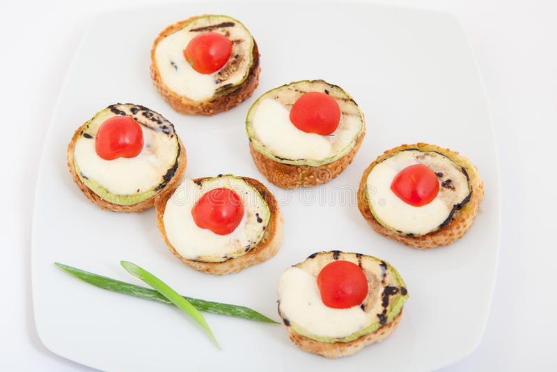 Bruschette (pain à l'ail grillé italien) avec la courgette, la tomate-cerise et le mozzarella image libre de droits