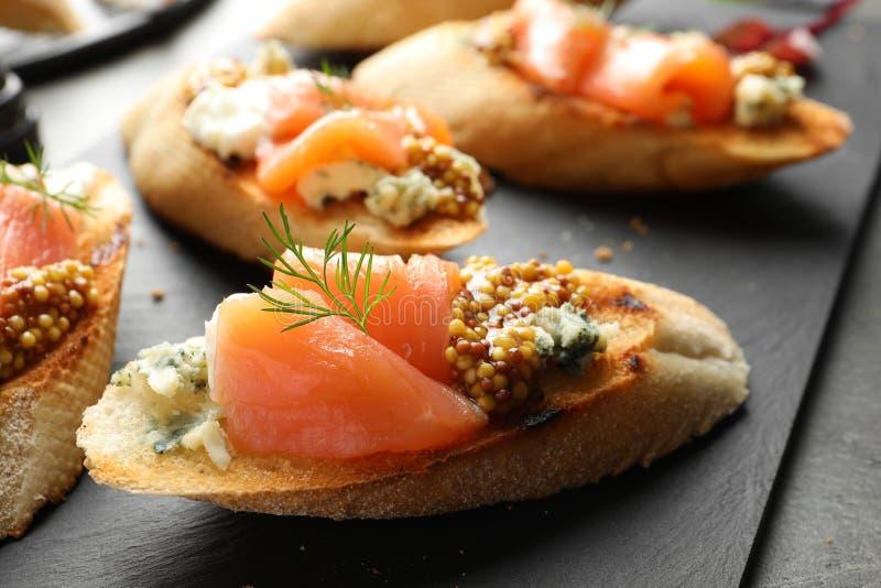 Bruschette saporite con formaggio di color salmone e blu sul piatto dell'ardesia fotografie stock libere da diritti
