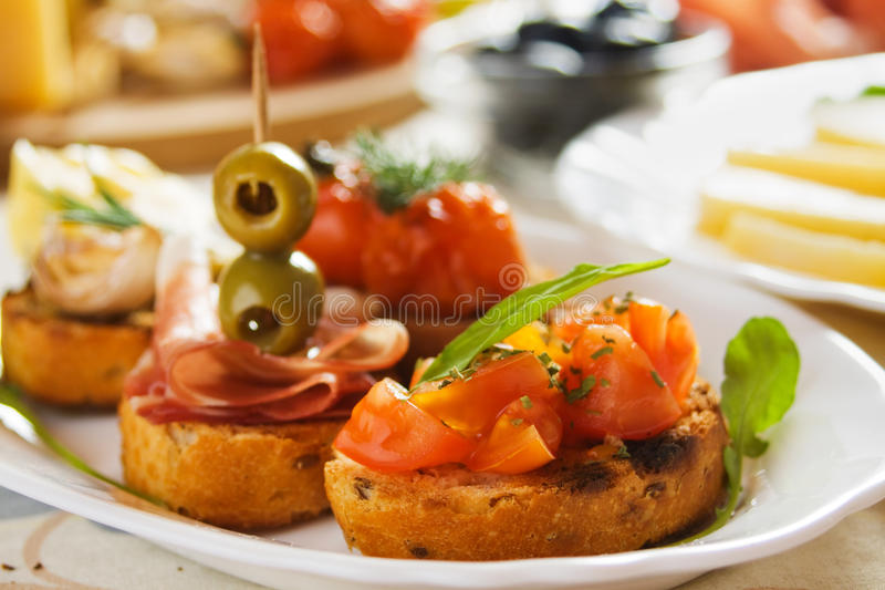Bruschette with tomato, olives and prosciutto. Italian canape, bruschette, with tomato, olives and prosciutto royalty free stock photography
