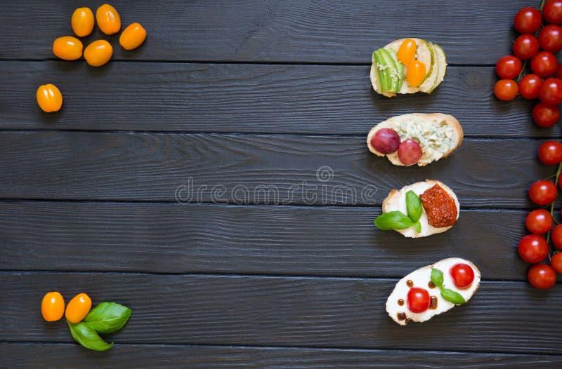 Bruschettes d'apéritif avec des tomates, saumons, fromage crémeux, basi photos stock