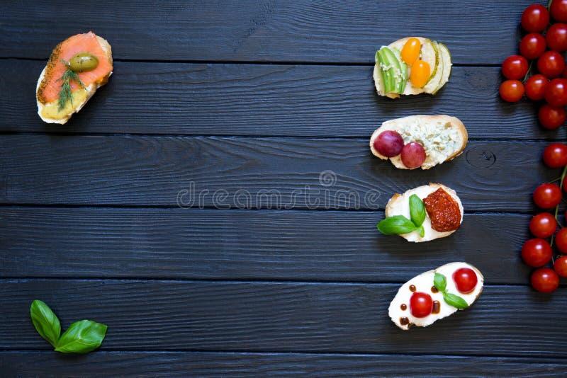 Bruschettes d'apéritif avec des tomates, saumons, fromage crémeux, basi photos libres de droits