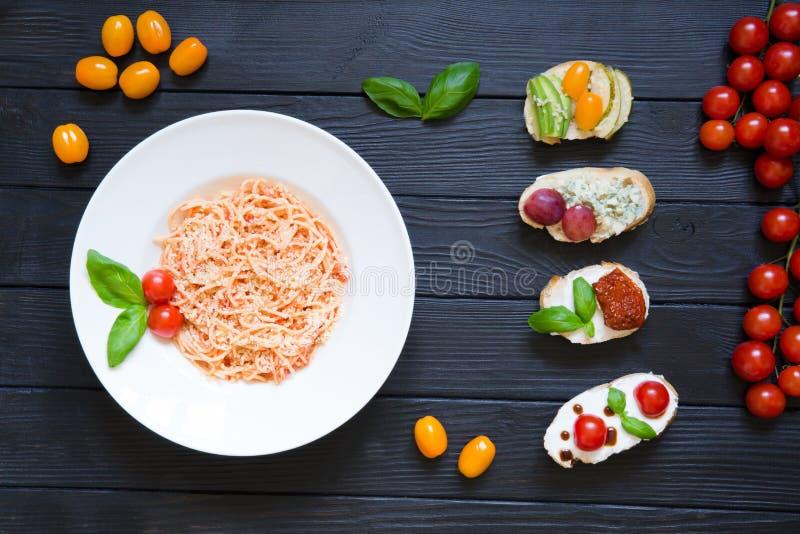 Bruschettes de spaghetti et d'apéritif avec des tomates, saumons, crème image libre de droits