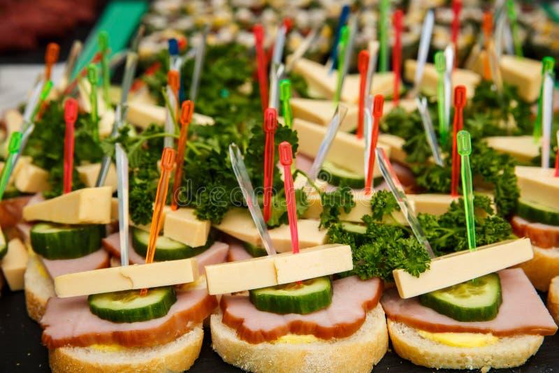 Bruschetti ou canapes com queijo, azeitonas, presunto, pepino fotos de stock