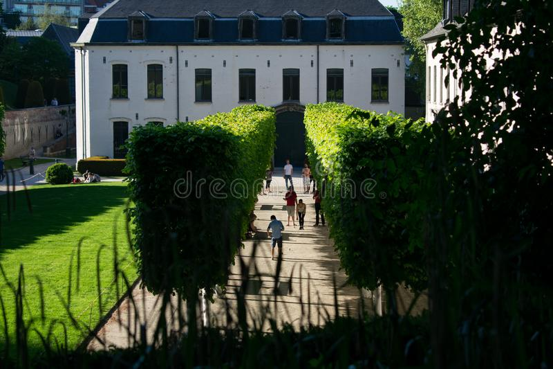 Bruselas, Bélgica - 6 de mayo de 2018: Parque de la abadía de Cambre del La el día soleado con la gente entre la fila de árboles foto de archivo libre de regalías