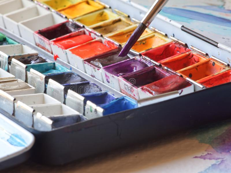 Watercolor box. Brush in a color of watercolor box royalty free stock photos