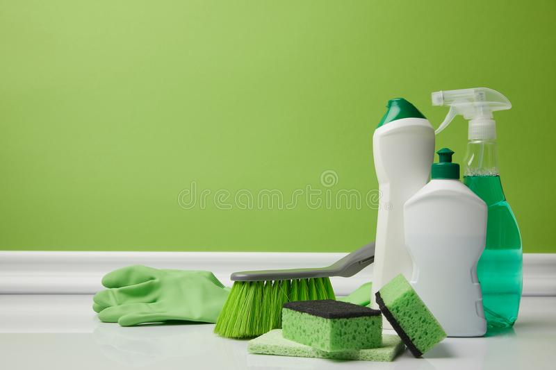 Brush and domestic supplies for spring cleaning. On green royalty free stock images