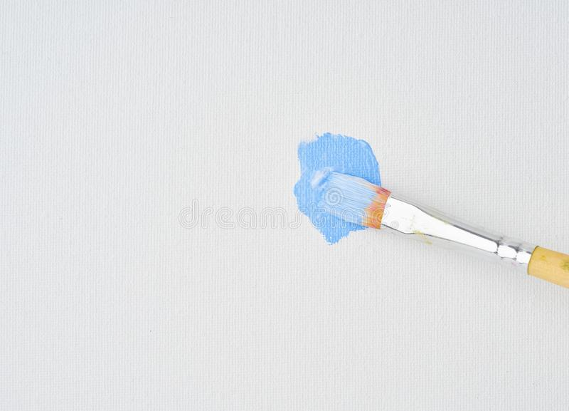 Brush draws blue paint on canvas, close up. Action painting art. Artist began to paint picture, first brushstrokes stock photography