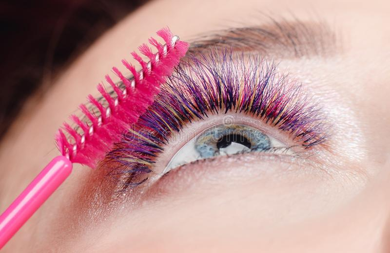Brush for eyelashes. Closeup of beautiful girl eye with make-up in beauty salon royalty free stock photos