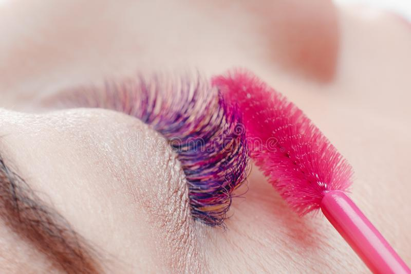 Brush for eyelashes. Closeup of beautiful girl eye with make-up in beauty salon stock photos